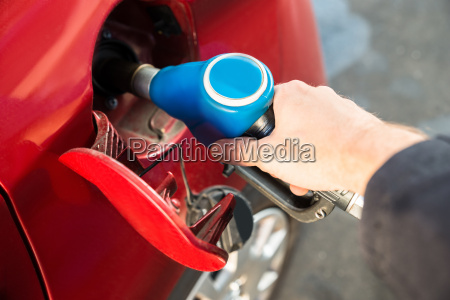 man refilling the car with fuel