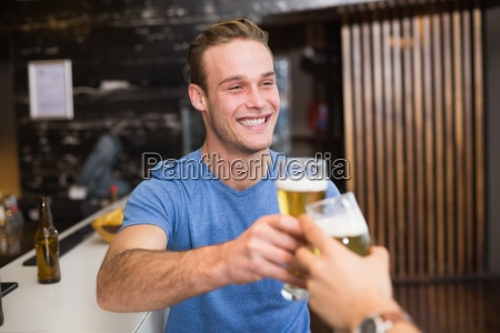 young man toasting with pint of
