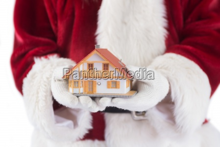 santa holds a tiny house in