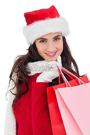 cheerful brunette in winter wear holding