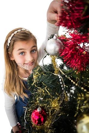 festive little girl decorating christmas tree