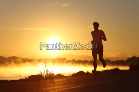 silhouette of a man running at