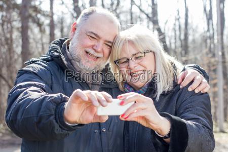 happy senior elderly couple taking selfie