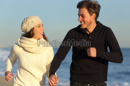 couple running on the beach in