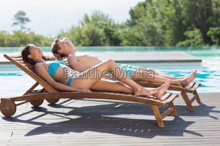 couple resting on sun loungers by