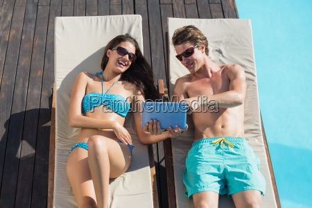 couple using digital tablet on sun