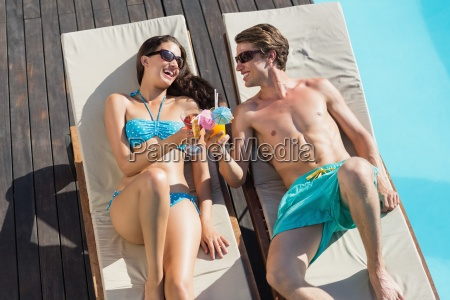 couple with drinks on sun loungers