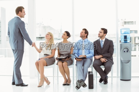 businessman shaking hands with woman besides