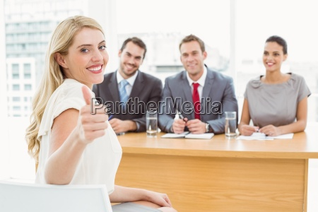 woman gesturing thumbs up in front