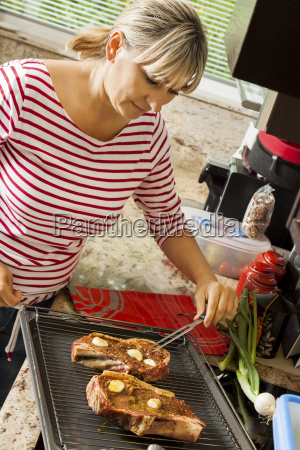 attractive blond woman prepares meat for