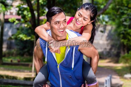 asian man carrying his girlfriend piggyback