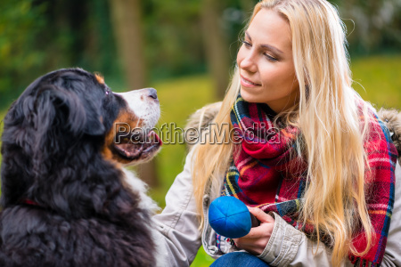 woman playing with dog in autumn