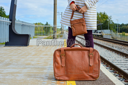 womans hands holding bag and suitcase