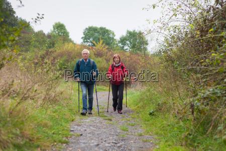 senior couple nordic walking on the