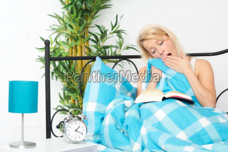young woman reading in bed reading