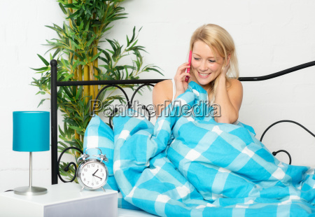 young woman sitting in bed at