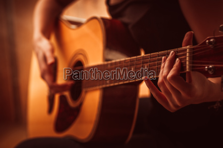 womans hands playing acoustic guitar close
