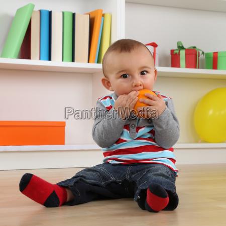 little baby eating an orange fruit