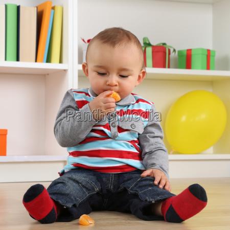 baby eating a mandarin fruit