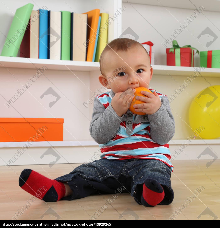 little, baby, eating, an, orange, fruit - 13929265