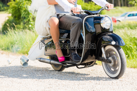 wedding couple driving scooter in wedding
