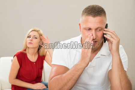 wife looking at husband talking on