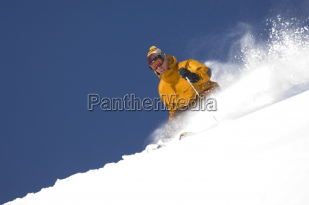 man skiing fresh powder in utah