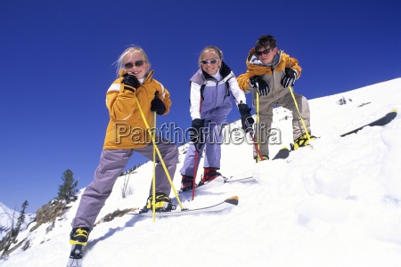 three kids smiling on the ski