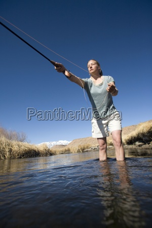 young woman fly fishing in bishop