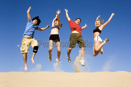 four young adults jumping atop a