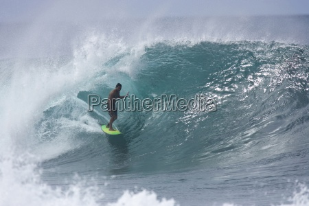 a young man surfing at pipeline