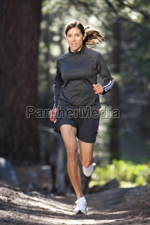 an athletic woman trail running in