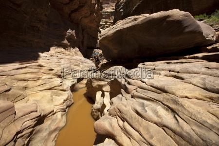 a woman hiking through a canyon