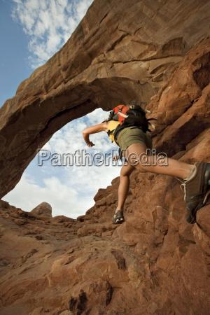 a woman jumps across rocks below
