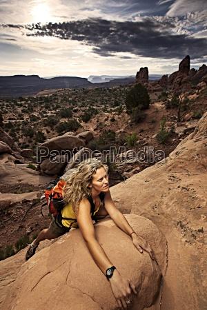 a woman scrambles up rocks in