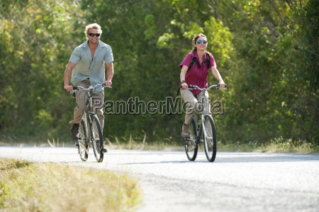 a couple ride bicycles in everglades