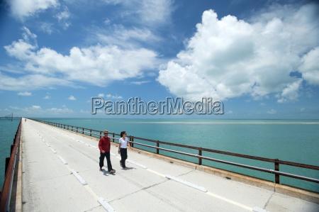 a couple walk along a bridge