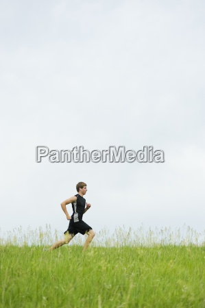 young man running on a grass