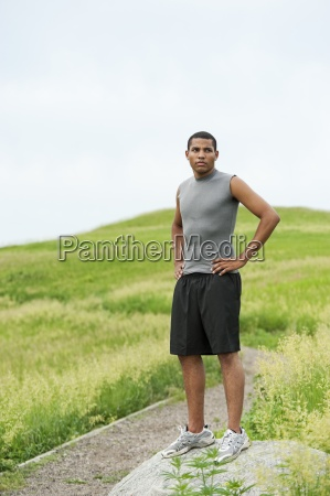 young man standing on rock after