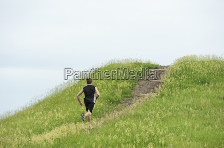 young man running up dirt trail