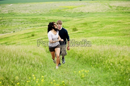 young couple running up a hill