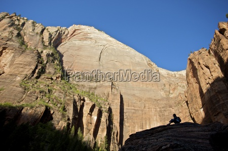 a hiker rests on a rock