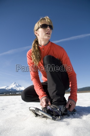 young, woman, straps, on, snowshoes, with - 13974283