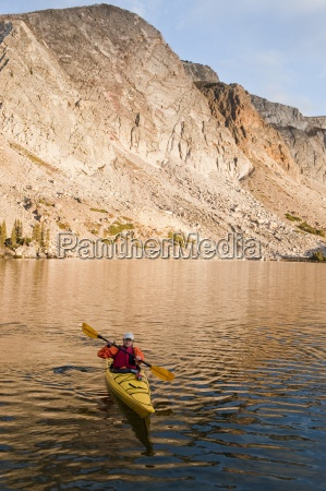 a man sea kayaking on lake
