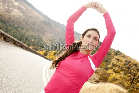 an athletic female stretches along a