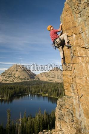 a man rock climbing above scout