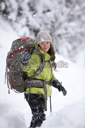 a young woman throws snow in