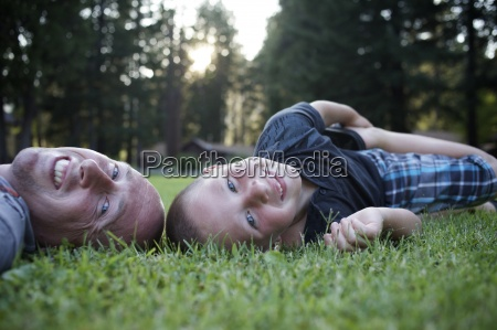 young boy lays in grass with