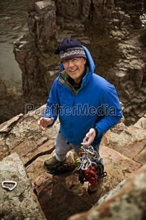 a man holds climbing gear and