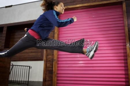 female runner leaps high in front